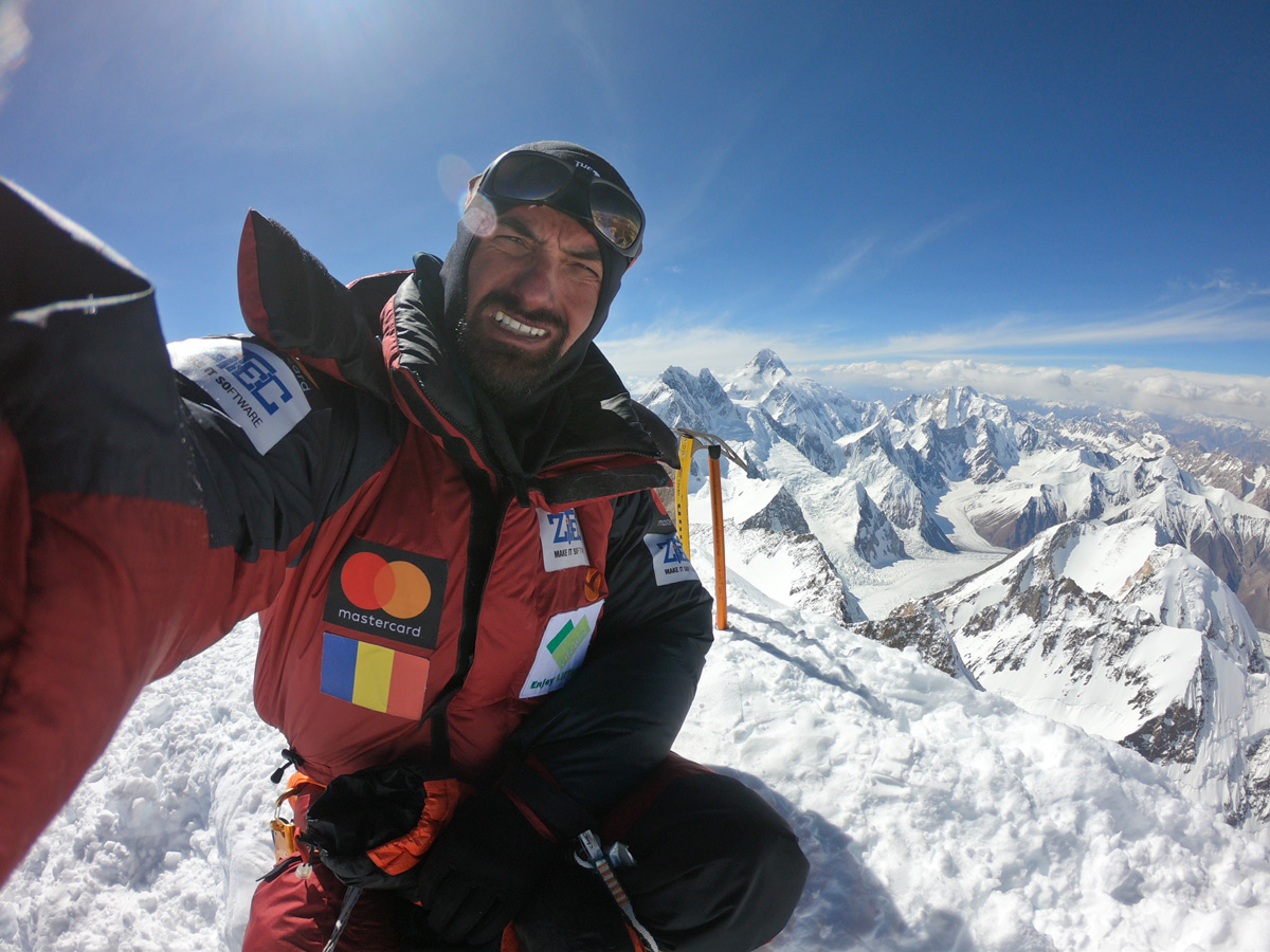 Caption Alex Gavan on the summit of Gashebrum 2 (8035m), july 2019, with Broad Peak (left, 8047m, which Alex summited back in 2014) and K2 the highest mountain visible in the background - Photo Alex Gavan